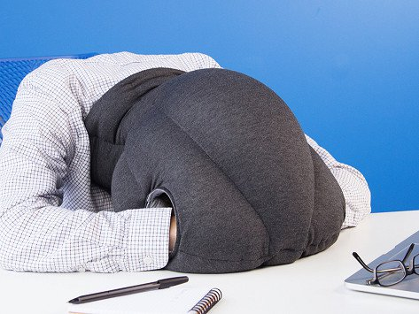 Man sleeping in an Ostrich pillow.