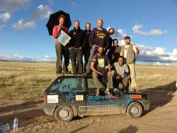 participants in the Mongol Rally stand on top of a dusty car