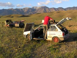 cars broken down in a field during the Mongolian Rally