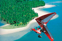 Airborne XT-912 Ultralight flying over an island