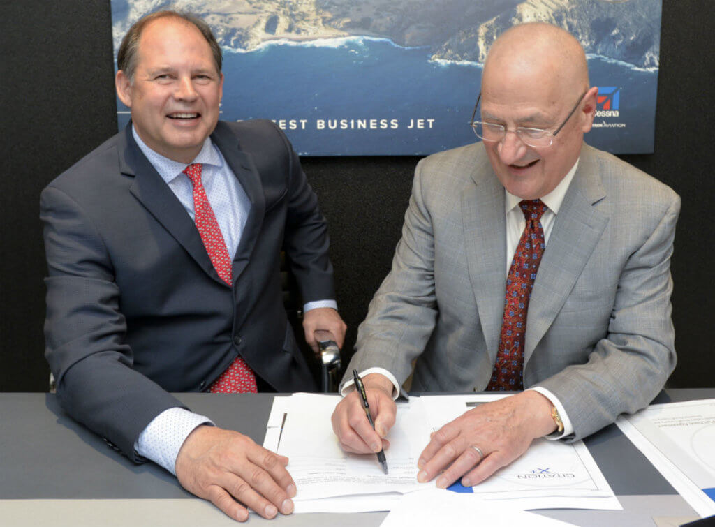 Textron Aviation president and CEO Scott Ernest (left) and Dr. Edmund O. Schweitzer III (right), president and chairman of the board, Schweitzer Engineering Laboratories, sign the contract for three Cessna Citation X+ business jets at NBAA 2016.
