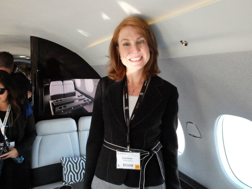 Kriya Shortt, Textron Aviation's vice-president of sales and marketing, shows off the 30-inch wide seats inside the Citaiton Hemipshere cabin mock-up at NBAA. Lisa Gordon Photo