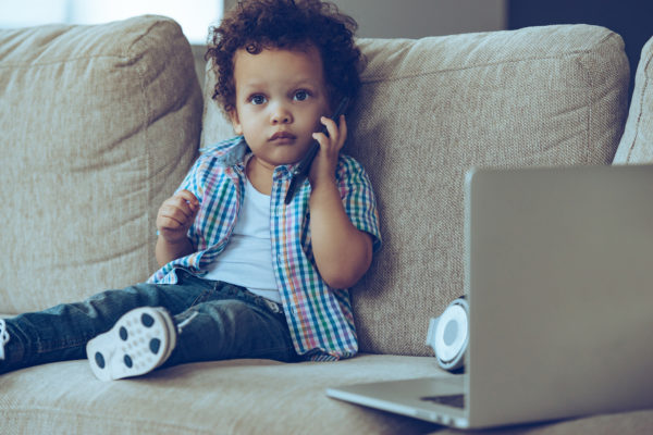 African-American baby boy talking on mobile phone and looking at camera while sitting on the couch at home