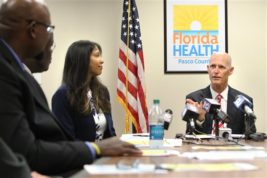 Florida Gov. Rick Scott, right, and Florida Surgeon General Dr. Celeste Philip, left, speak with local officials during a Zika Preparedness Roundtable at the Florida Department of Health of Pasco County, Tuesday, Aug. 23, 2016, in New Port Richey, Fla. Scott on Tuesday announced a non-travel-related case of Zika in the Tampa Bay region. (Brendan Fitterer/Tampa Bay Times via AP)