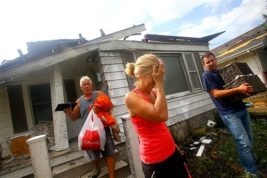 Cindy Ropes comes out of her house as friend Stan Carter and son Ryan Ropes help her clear personal items from the house in Kokomo, Ind., Wednesday, Aug. 24, 2016. Multiple tornadoes touched down in central Indiana on Wednesday, tearing the roofs off apartment buildings, sending air conditioners falling onto parked cars and cutting power to thousands of people. (Tim Bath/The Kokomo Tribune via AP)