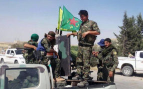 FILE - In this file photo released on Tuesday, June 23, 2015, provided by the Kurdish fighters of the People's Protection Units (YPG), which has been authenticated based on its contents and other AP reporting, Kurdish fighters of the YPG, sit on their pickup in the town of Ein Eissa, north of Raqqa city, Syria. A Turkish military expedition into Syria has threatened a Kurdish political project just as Kurdish forces seemed on the verge of connecting their northern Syrian zones. It is the first Turkish ground intervention in the course of the Syria war, now in its sixth year, and it underscores how seriously Turkey is taking Kurdish autonomy next door. (The Kurdish fighters of the People's Protection Units via AP, File)