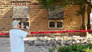 Steve Gibson, of Pawnee, takes photos of damage to a building in downtown Pawnee, Okla., following a 5.6 magnitude earthquake that hit just after 7 a.m., in north-central Oklahoma, Saturday, Sept. 3, 2016. (David Bitton/The News Press via AP)