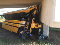 In this Sunday, Sept. 11, 2016 photo provided by the Denver Police Department a bus sits after crashing into a concrete pillar at Denver International Airport in Denver. The school bus driver was killed Sunday and several others were injured after the bus veered off a roadway, police said. (Denver Police Department via AP)