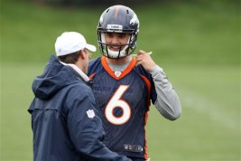 Denver Broncos rookie quarterback Brock Osweiler, back, jokes with an unidentified coach during a break in drills during the Broncos' NFL football rookie minicamp at the team's training headquarters in Englewood, Colo., on Saturday, May 12, 2012. (AP Photo/David Zalubowski)