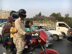 A family travels by motorcycle in Islamabad.