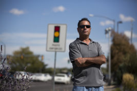 Kelly Gonzales poses for a photo near the intersection of South Chambers Road and East Mississippi Avenue on Friday Sept. 23, 2016. Gonzales says that the city's signs warning of photo red light cameras are inappropriately placed. Photo by Gabriel Christus/Aurora Sentinel
