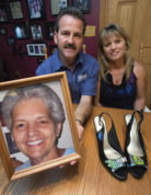 """This Aug. 11, 2016 photo shows Jimmy Trout and his wife Cynthia with a photograph of Jimmy's mother, Ann Sue Metz, who was murdered in Frederick in 2009, in Frederick, Md. Jimmy wears the high heels that have """"Mom"""" written on the toe in the yearly """"Walk a Mile in Her Shoes"""" fundraiser for the Hartley House, a facility in Frederick that provides services for victims of domestic violence.  (Dan Gross/The Frederick News-Post via AP)"""