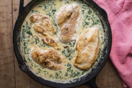This August 2016 photo shows chicken with spinach in cream sauce. This dish is from a recipe by Katie Workman. (Sarah E. Crowder via AP)