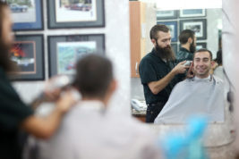 Kenneth Miller, owner of Ivan's Barber Shop, cuts Sean Wollman's hair Oct. 4 at Ivan's Barber Shop. Miller, like many other business owners, regards a bad review as valuable information that can help improve business. Photo by Gabriel Christus/Aurora Sentinel