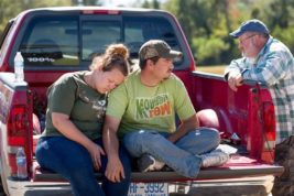 From left, Jennifer Bibey, DJ Bryant and Rickey Bibey rest on the back of a pick up truck after being evacuated from their homes Tuesday, Oct. 11, 2016 in Vass, N.C. Residents in harms way of a potential Woodlake Dam failure were notified of a mandatory evacuation last night. The Bibey's and Bryant opted out of staying in a shelter because they would not be able to bring their pets with them. (Jill Knight/The News & Observer via AP)