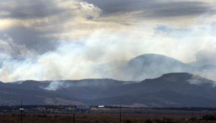 Smoke rises from the southern end of a wildfire in the late afternoon Tuesday, Oct. 18, 2016, near Wetmore, Colo. (Chris McLean/The Pueblo Chieftain via AP)