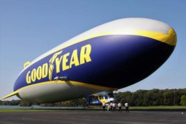 This Oct. 6, 2016 photo shows Goodyear's newest airship, Wingfoot Two, in Mogadore, Ohio.  Goodyear is officially welcoming Wingfoot Two, the second airship in the fleet replacing its famous blimps.   The first of the new models, Wingfoot One was launched in 2014.   From the ground, the cigar-shaped replacements look much like their predecessors. Though they still use helium and bear the blue-and-gold Goodyear logo, they aren't technically blimps because they have a fixed structure holding the balloon in place.  (Malcolm Porter/WEWS-TV via AP)