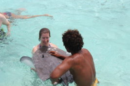 In this Nov. 2, 2015 photo courtesy of Jennifer McDermott, Associated Press writer Jennifer McDermott holds an older, docile stingray with help from a tour guide in Bora Bora. Bora Bora offers celebrity-style seclusion and has been a vacation destination for the likes of Justin Bieber, Jennifer Aniston and Usain Bolt. It's located 160 miles from Tahiti with a balmy and relatively consistent temperature of 80 degrees Fahrenheit. (Courtesy of Jennifer McDermott via AP)