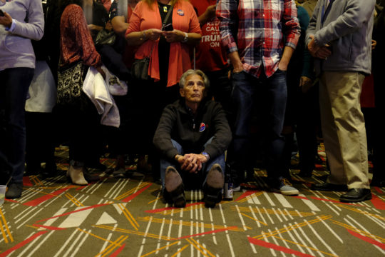 Doug Barnes sits patiently on the floor as election results are reported during the GOP watch party Nov. 8, at the Doubletree Hotel in the Denver Tech Center. (Photo by Philip B. Poston/Aurora Sentinel)
