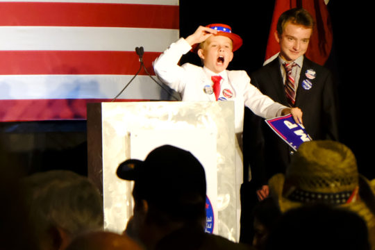 Dalton Walker, 13, left, and Jacob Lynch, 14, celebrate on stage and the electorate votes continued to grow for Donald Trump at the GOP watch party Nov. 8, at the Doubletree Hotel in the Denver Tech Center. (Photo by Philip B. Poston/Aurora Sentinel)
