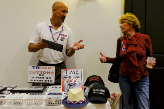 "Trump supporters Jim Maser and Stephanie DeGraf Bender discuss early voting projections outside of the GOP watch party Nov. 8, at the Doubletree Hotel in the Denver Tech Center. Jim the ""Pin man"" was selling Trump memorabilia throughout the evening. (Photo by Philip B. Poston/Aurora Sentinel)"