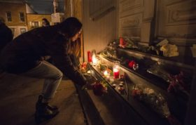 "A woman places a candle in front of the home of singer and poet Leonard Cohen, Thursday, Nov. 10, 2016 in Montreal. Cohen, the baritone-voiced Canadian singer-songwriter who seamlessly blended spirituality and sexuality in songs like ""Hallelujah,"" ""Suzanne"" and ""Bird on a Wire,"" has died at age 82.  (Paul Chiasson/The Canadian Press via AP)"