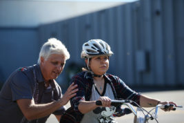 Gene Hodges, owner of Treads, helps Aurora Magazine staff writer Susan Gonzalez learn to ride a bike - with nominal success - in a parking lot behind the shops at Iliff Avenue and Buckley Way.