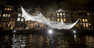 The Lace, an art work by Choi+Shine Architects, based in Brookline, MA., U.S.A., is suspended over Herengracht canal as part of the Amsterdam Light Festival, Netherlands, Wednesday, Nov. 30, 2016. The festival opens on Dec. 1, 2016, and ends on Jan. 22, 2017, the artworks are lit from 17:00 until 23:00, and for the Illuminade, a walking route, between 17:00 and 22:00 Central European Time. (AP Photo/Peter Dejong)