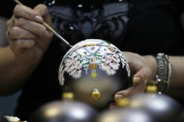 In this photo taken on Thursday, Nov. 24, 2016, an artisan paints Christmas decorations in the Christmas decorations museum in Klin, about 85 kilometers (53 miles) northwest of Moscow.  (AP Photo/Pavel Golovkin)