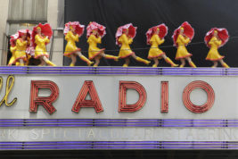 "FILE – In this June 7, 2016, file photo, dancers from the Radio City Rockettes promote their ""New York Spectacular"" show by performing on the marquee of Radio City Music Hall in New York. The slow recovery of the U.S. economy is keeping the cost of gifts listed in the song ""The Twelve Days of Christmas"" from spiraling out of control, according to Pittsburgh-based PNC Financial Services Group's 33nd annual ""PNC Wealth Management Christmas Price Index"" released Thursday, Dec. 1, 2016. (AP Photo/Richard Drew, File)"