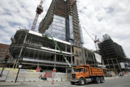 In this Thursday, May 19, 2016, photo, a dump truck drives past the construction site of a high-rise building in Boston. On Thursday, Dec. 1, 2016, the Commerce Department reports on U.S. construction spending in October 2016. (AP Photo/Steven Senne)