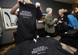 "FILE - In this Nov. 8, 2016, file photo, Kathy Schmitt, left, folds T-shirts that she designed, declaring ""Madam President,"" for sale at an election night party for Democrats in Seattle. Copies of a one-off edition of Newsweek featuring Hillary Clinton that carried the title ""Madam President"" that were recalled following Clinton's loss in the Nov. 8, 2016, election are being sold for hundreds of dollars on eBay. (AP Photo/Elaine Thompson, File)"