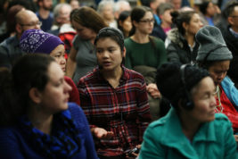 Khin Than translates the panel discussion on immigrant rights, policies and mental health for the Burmese speaking attendants on Thursday Dec. 01, 2016 at Aurora Central High School. Photo by Gabriel Christus/Aurora Sentinel
