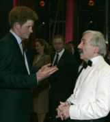 FILE - In this Wednesday, Nov. 12, 2008 file photo, Britain's Prince Harry talks to British actor Andrew Sachs backstage at the Wimbledon Theatre after a charity performance in aid of the Prince's Trust charity, in London. Comic actor Andrew Sachs, known primarily for his role as Manuel in the 1970s situation comedy Fawlty Towers, has died it was announced Thursday, Dec. 1, 2016. He was 86 and had been suffering from vascular dementia. (AP Photo/Alastair Grant, file)
