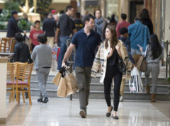 FILE - In this Friday, Nov. 25, 2016, file photo, Eric Denker and his wife, Jalen Denker, of Irvine, take advantage of sales to buy suits for business school interviews at South Coast Plaza in Costa Mesa, Calif. On Friday, Dec. 2, 2016, the U.S. government issues the November jobs report. (Jeff Gritchen/The Orange County Register via AP, File)