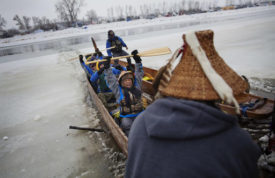 In this Thursday, Dec. 1, 2016 photo, Virginia Redstar of Colville, Wash., and a member of the Colville Native American tribe, celebrates upon reaching shore by canoe at the Oceti Sakowin camp where people have gathered to protest the Dakota Access oil pipeline in Cannon Ball, N.D. Redstar traveled from Montana with fellow tribal members on canoe for 10 days down the Missouri river to reach the camp. (AP Photo/David Goldman)