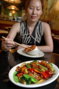 FILE- In this July 22, 2004 file photo, Tong Xian Mei, of Ollie's Restaurant, samples from a plate of General Tso's Chicken in New York. Chef Peng Chang-kuei, the chef who has been credited with inventing world-famous Chinese food staple that is not served in China, has died, Wednesday, Nov. 30, 2016. He was 98. (AP Photo/Richard Drew, File)