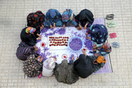 In this picture taken on Tuesday, Nov. 1, 2016, Iranian farm workers separate the crimson stigmas from the purple blossoms in the courtyard of a house just outside the city of Torbat Heydariyeh, southeastern Iran. It's a brilliant patchwork of color as the women open thousands of purple crocus flowers and, from each, separate out three delicate, tiny and extremely valuable red threads: It's Iran's harvest for saffron, lauded as the world's most expensive spice. (AP Photo/Ebrahim Noroozi)