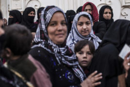 Iraqi women stand while waiting for aid to be distributed, in the Samah district of Mosul, Iraq, Sunday, Dec. 4, 2016. (AP Photo/Manu Brabo)