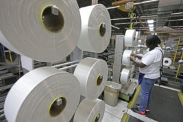 FILE - In this Friday, Oct. 21, 2016, file photo, Barbara Taylor examines a spool of thread made from recycled plastic bottles at the Repreve Bottle Processing Center, part of the Unifi textile company, in Yadkinville, N.C. On Tuesday, Dec. 6, 2016, the Commerce Department reports on U.S. factory orders for October. (AP Photo/Chuck Burton, File)