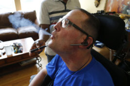 "In this Aug. 21, 2015 photo, multiple sclerosis patient and author of the memoir ""One day at a Time,"" David Sloan, who is a medical marijuana patient, exhales smoke from medical cannabis concentrate given to him with help from his caregiver, at Sloan's home in Highlands Ranch, south of Denver. Marijuana researchers have predominantly looked at how the drug affects young, developing brains. But increased pot use by older adults has scientists calling for more study of how aging influences drug use, and whether elderly pot users face potential health benefits or risks. (AP Photo/Brennan Linsley)"