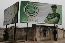 """In this picture taken Monday, Dec. 5, 2016, a Syrian man walks by posters of Syrian President Bashar Assad with Arabic that read """"Homeland, honor, fidelity. Together we will build it,"""" in Aleppo, Syria. A Syrian war monitoring group says government forces have captured large parts of Aleppo's central-eastern al-Shaar neighborhood from rebels. The Britain-based Syrian Observatory for Human Rights says government forces took most of the once-populous neighborhood Tuesday following intense clashes. (AP Photo/Hassan Ammar)"""