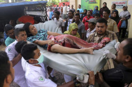 Hospital workers and family members carry a woman injured in an earthquake at a hospital in Pidie, Aceh province, Indonesia, Wednesday, Dec. 7, 2016. A strong undersea earthquake rocked Indonesia's Aceh province early on Wednesday, killing a number of people and causing dozens of buildings to collapse. (AP Photo/Heri Juanda)