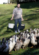 Fois gras producer Robin Arribit carries food for ducks at his farm in La Bastide Clairence, southwestern France, Wednesday, Dec.7, 2016. The French Agriculture Ministry raised from moderate to high its risk assessment for bird flu on Tuesday across the country, while foie gras is a traditional Christmas Eve meal. (AP Photo/Bob Edme)