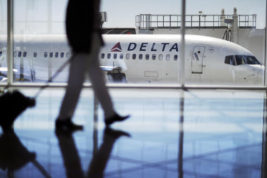 In this Thursday, Oct. 13, 2016, photo, a Delta Air Lines jet sits at a gate at Hartsfield-Jackson Atlanta International Airport in Atlanta. Delta announced Thursday, Dec. 8, 2016, that the airline is rolling out new free snacks for customers in the main cabin, including brand-name yogurt bars and pretzels. Some will come in larger portions than before because, Delta has figured out, that's what customers crave. (AP Photo/David Goldman)