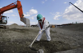 FILE - In this Feb. 10, 2016 file photo, a worker, wearing a protective suit and a mask, levels ground at the tsunami-crippled Fukushima Dai-ichi nuclear power plant, operated by Tokyo Electric Power Co. (TEPCO), in Okuma, Fukushima Prefecture, northeastern Japan, one month before Japan marks the fifth anniversary of a devastating earthquake and tsunami that left nearly 19,000 people dead or missing, turned coastal communities into wasteland and triggered a nuclear crisis. A cost estimate to clean up Japan's wrecked Fukushima nuclear plant has doubled to nearly 22 trillion yen ($190 billion), with decommissioning costs expected to continue to rise, according to a government panel Friday, Dec. 9, 2016. (Toru Hanai/Pool Photo via AP, File)