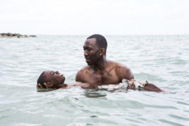 """This image released by A24 shows Alex Hibbert, foreground, and Mahershala Ali in a scene from the film, """"Moonlight."""" The film was nominated for a Golden Globe award for best motion picture drama on Monday, Dec. 12, 2016. The 74th Golden Globe Awards ceremony will be broadcast on Jan. 8, on NBC. (David Bornfriend/A24 via AP)"""