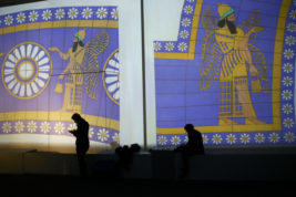 Visitors look on in the Palmyra Exhibit, a three-dimensional projection featuring never-before-seen images of Palmyra taken by a drone in April after the city was liberated from IS fighters, at Grand Palais in Paris, Tuesday, Dec.13, 2016. As Islamic State extremists recapture the ancient Syrian city of Palmyra, the French president and the UNESCO chief are inaugurating an exhibit in Paris to educate the public about the wonders of endangered UNESCO heritage sites in Palmyra and the Middle East. (AP Photo/Francois Mori)