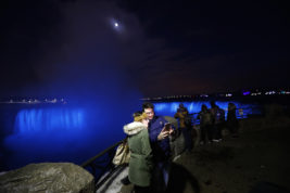 In this Saturday, Dec. 10, 2016 photo, people take a selfie near the Niagara Falls illuminated by new LED lights, in Niagara, Ontario. The bright sight of the natural wonder all lit up draws tourists despite the region's dark, cold winter nights. (AP Photo/Julio Cortez)