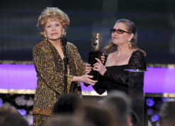 FILE- In this Jan. 25, 2015, file photo, Carrie Fisher, right, presents her mother Debbie Reynolds with the Screen Actors Guild life achievement award at the 21st annual Screen Actors Guild Awards in Los Angeles. Reynolds' death certificate obtained Tuesday, Jan. 10, confirms that the actress died of a stroke. (Photo by Vince Bucci/Invision/AP, File)